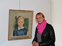 Cecilia Thaning in front of the portrait of her father Gunnar