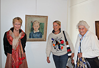 Eva Rosenqvist, Marianne Thaning and Anna-Stina Thaning in front of the portrait of Gunnar Thaning